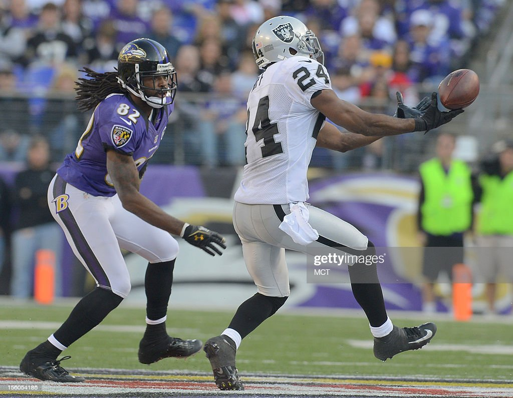 Baltimore Ravens wide receiver Torrey Smith can't come up with a reception, and nearly gets the pass picked off by tipping it in the air as Oakland Raiders cornerback Michael Huff defends in Baltimore, Maryland, on Sunday, November 11, 2012.