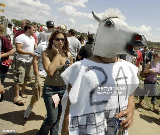 A racing fan dressed in a horses head mask walks through the infield before the 131st Preakness Stakes at Pimlico Race Course in Baltimore Maryland...