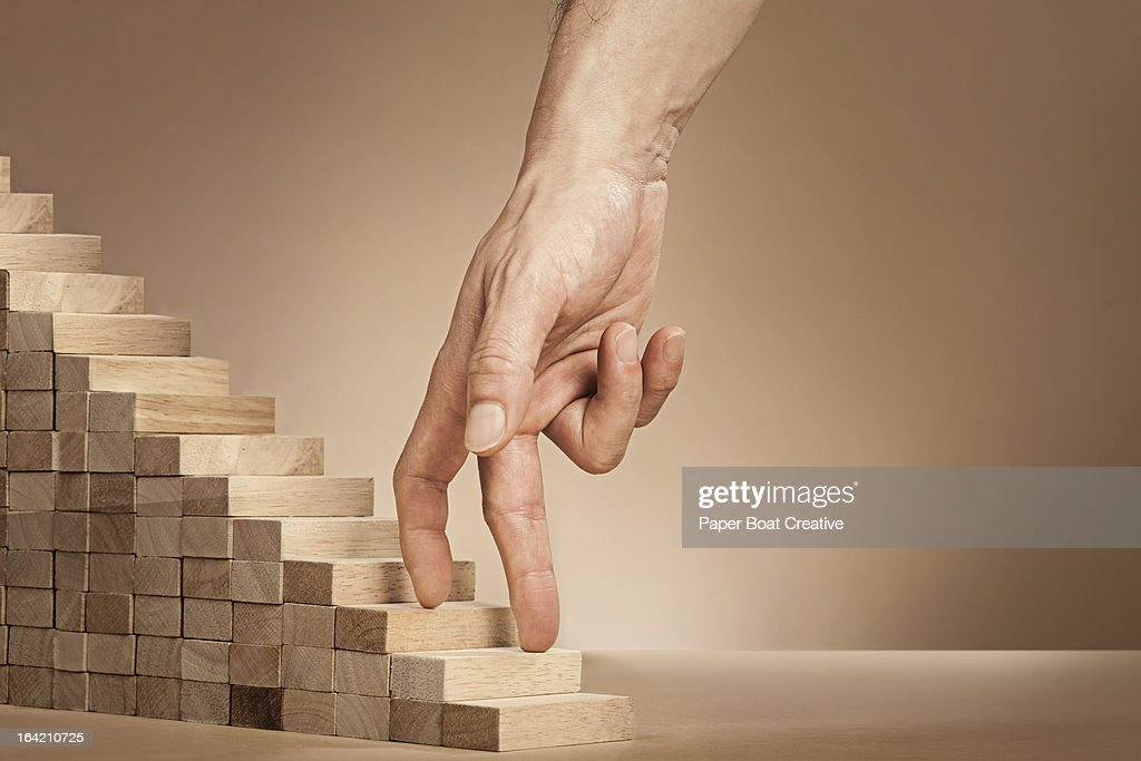 baMan's hand climbing stairs made of wooden blocks