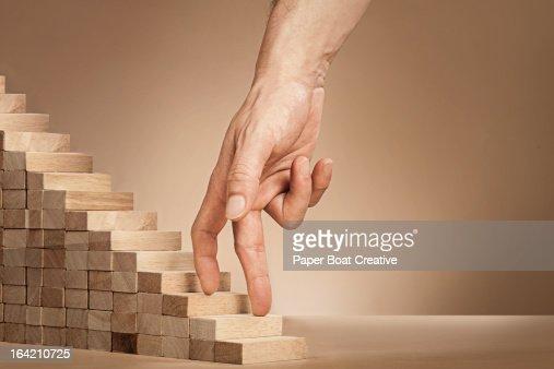 baMan's hand climbing stairs made of wooden blocks : Stock Photo