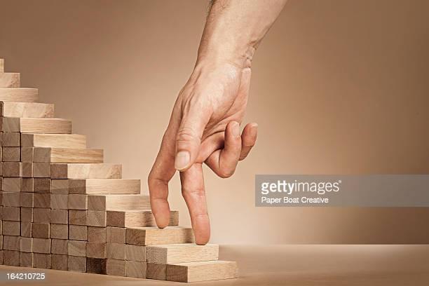 baMan's hand climbing stairs made of wooden blocks