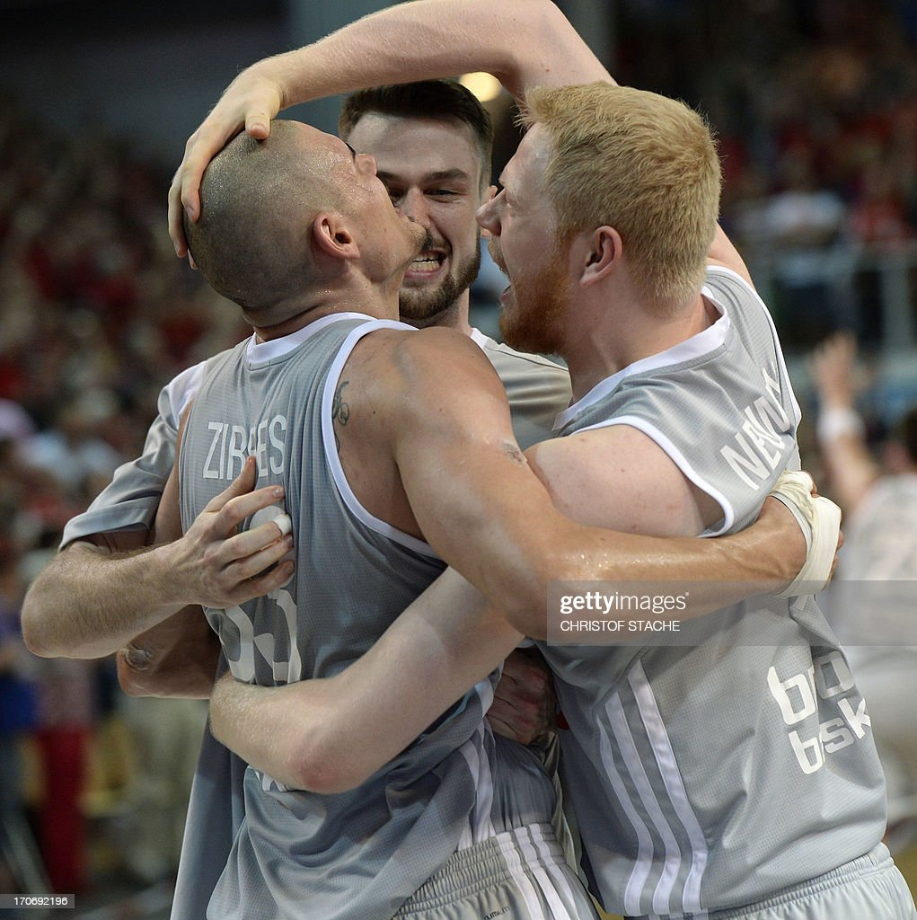 Bamberg's Maik Zirbes, Andrew James Ogilvy and Philipp Neumann celebrate after the German first division basketball Bundesliga final play off match between Brose Baskets Bamberg and EWE Baskets Oldenburg in Bamberg, southern Germany, on June 16, 2013. Bamberg won the match 91-88.