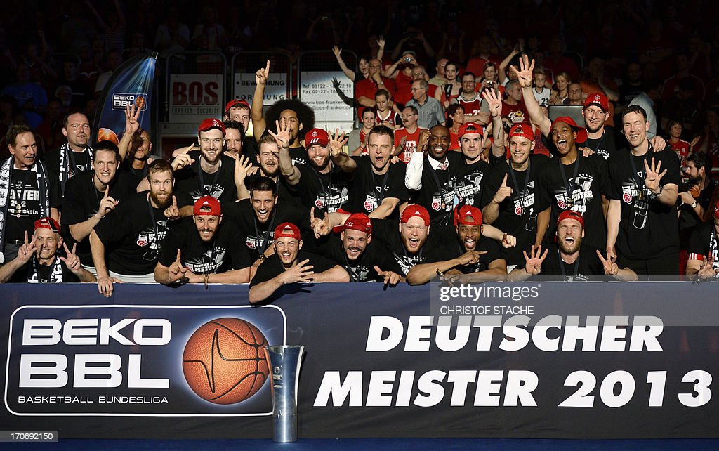 Bamberg's team members celebrate with the trophy of the German first division basketball Bundesliga after they won the third final play off match between Brose Baskets Bamberg and EWE Baskets Oldenburg in Bamberg, southern Germany, on June 16, 2013.