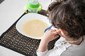 Bambino seduto a tavola che non vuole mangiare, mani sul viso in modo pensieroso