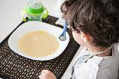 Bambino a tavola che mangia la pappa da solo