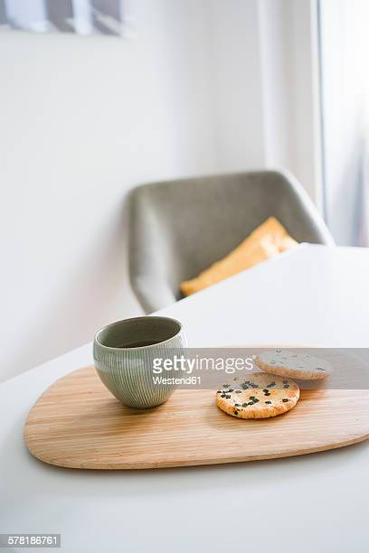Bamboo board with bowl of Japanese green tea and two rice crackers
