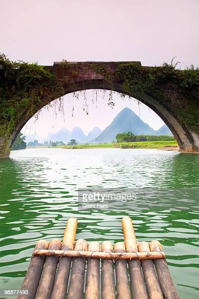 bamboo raft headng towards a stone bridge