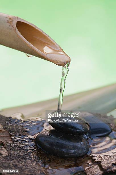 Bamboo spout pouring water over stack of black pebbles
