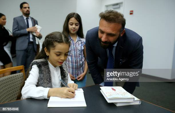 Bana Alabed the 8yearold Syrian girl who fled to Turkey from the wartorn Syrian city of Aleppo signs her book named 'Dear World A Syrian Girl's Story...