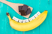 Banana, dark chocolate and wooden cubes on an aqua colored table. They symbolize rich magnesium food.