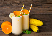 Banana and orange smoothies in the morning on a white wooden floor.