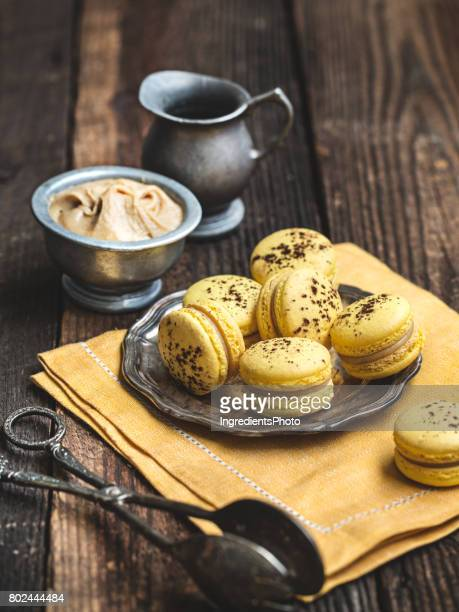 Banana macarons on a rustic wooden table.