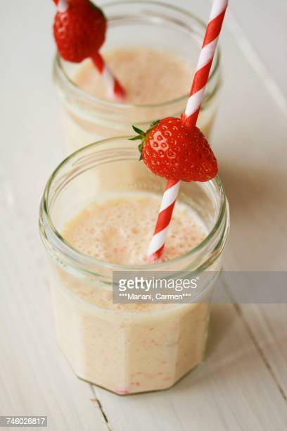 Banana milkshakes with straws and a strawberries