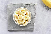 Healthy organic snack. Natural food or vegetarian vegan food concept. Banana slices in bowl. Top view, flat lay