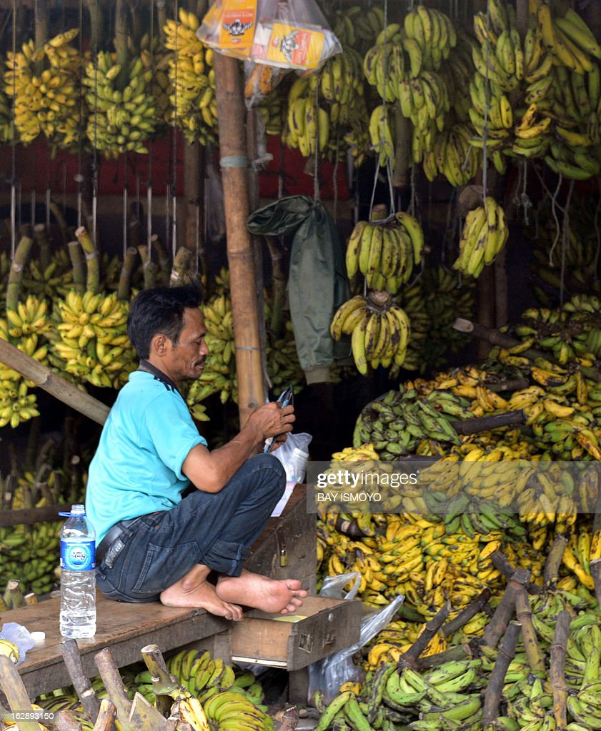 A banana vendor uses his cell phone while waiting for costumers at his kiosk at Babakan market in Tangerang, Banten province, on March 1, 2013. Indonesian inflation in February hit a 20-month high after government measures to limit commodity imports pushed up consumer prices, an official said. AFP PHOTO / Bay ISMOYO