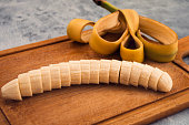 Banana with a white core, cut into thin slices, peeled, stacked beautifully on a wooden background.