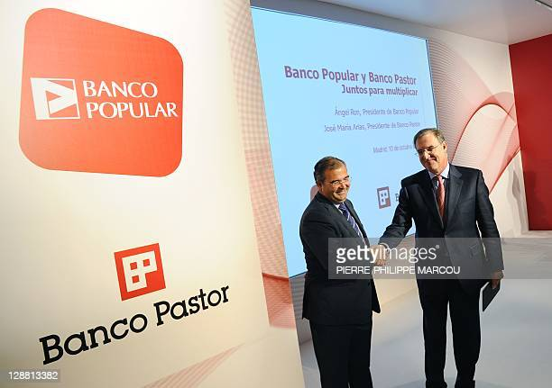 Banco Popular's chairman Angel Ron shakes hand with Banco Pastor's chairman Jose Maria Arias before giving a press conference in Madrid on October 10...