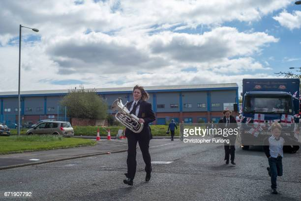 A band band player runs to catch up the rest of the band during the Manchester St George's Day parade through the streets on April 23 2017 in...