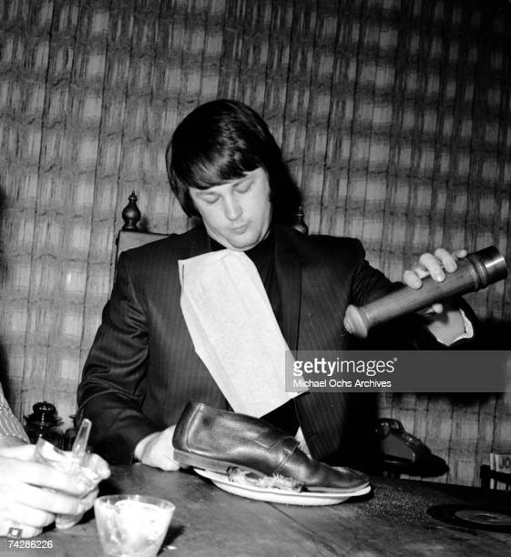 Band leader Brian Wilson of the rock and roll band 'The Beach Boys' chomps variously down on a record a shoe other people's food a pepper grinder and...