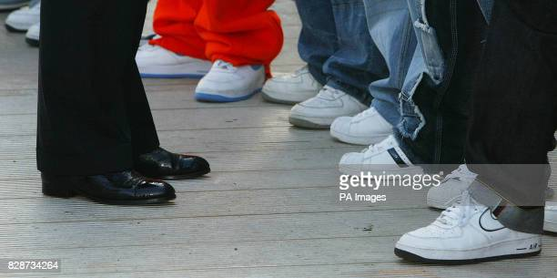 Band members of pop band Blazin Squad wearing trainers greet Prince Charles who is wearing leather shoes as he meets artists backstage during the...