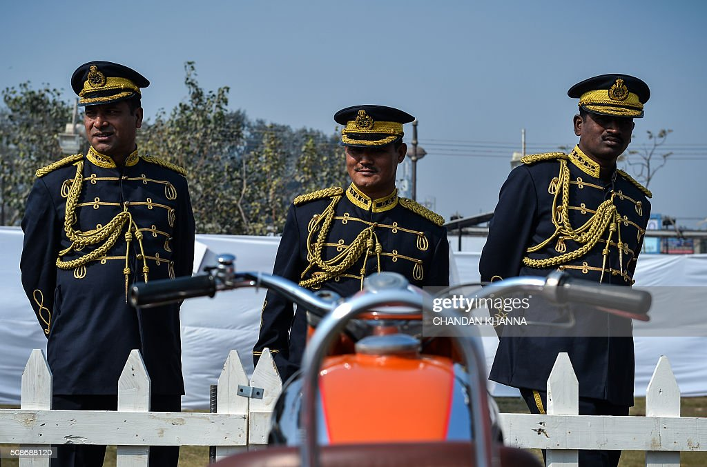 Band members of the Central Industrial Security Force (C.I.S.F) look on next to a vintage motorcycle at the 6th 21 Gun Salute International Vintage Car Rally in New Delhi on February 6, 2016. The two-day event ends February 7. AFP PHOTO / CHANDAN KHANNA / AFP / Chandan Khanna