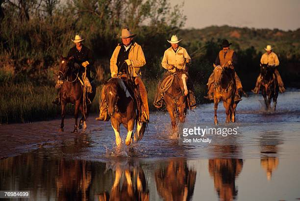 A band of cowboys on horseback gallop through a stream in 1996 at the Double Mountain River Ranch outside Rotan TX Cowboy life in 1996 was much the...