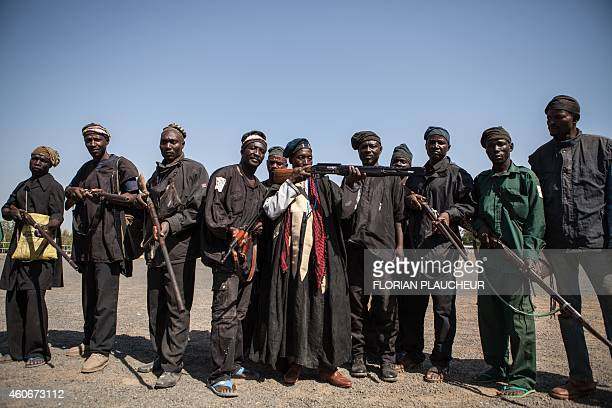 A band of hunters pose in Yola state capital of Adamawa on December 4 2014 after taking part in an operation against Nigerian Islamist extremist...