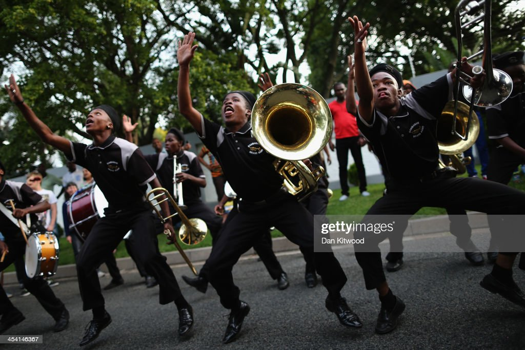 A band plays outside the Houghton home of the former South African President Nelson Mandela on December 7, 2013 in Johannesburg, South Africa. Mandela, also known as Madiba, passed away on the evening of December 5th, 2013 at his home in Houghton at the age of 95. Mandela became South Africa's first black president in 1994 after spending 27 years in jail for his activism against apartheid in a racially-divided South Africa.