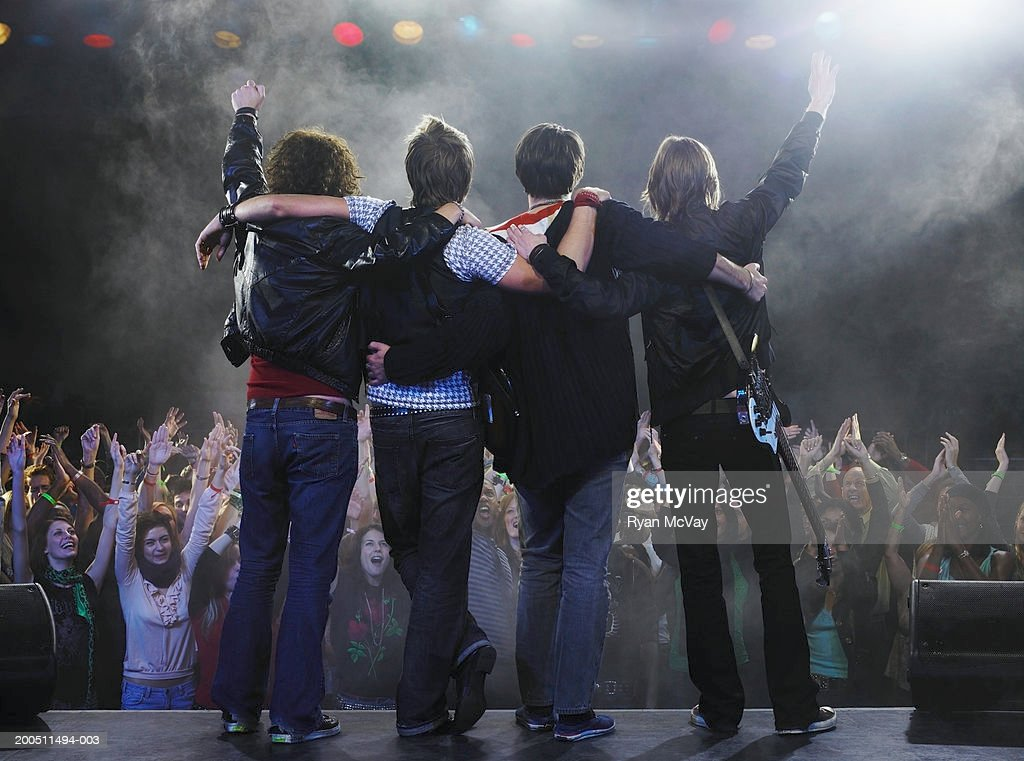 Band standing before audience on stage with arms around each other