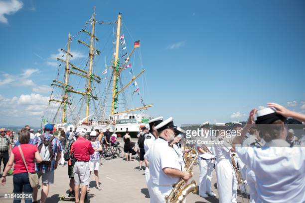 A band stnds near a ship that is taking part in the Tall Ships regatta marking the 150th anniversary of Canada's founding in Quebec City on July 18...