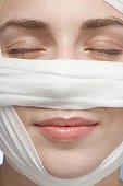 Bandage around woman's face, close-up