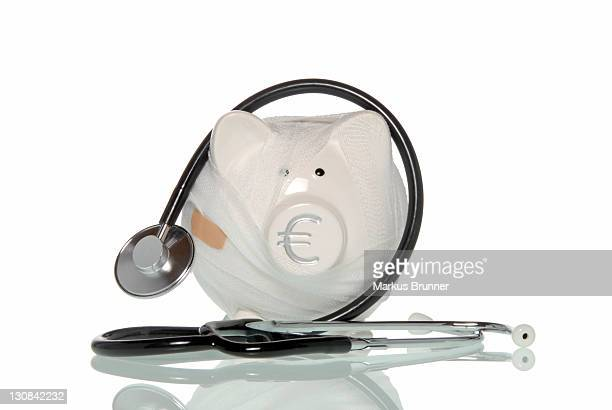 Bandaged piggy bank with a stethoscope, symbolic image for health insurance companies in financial distress