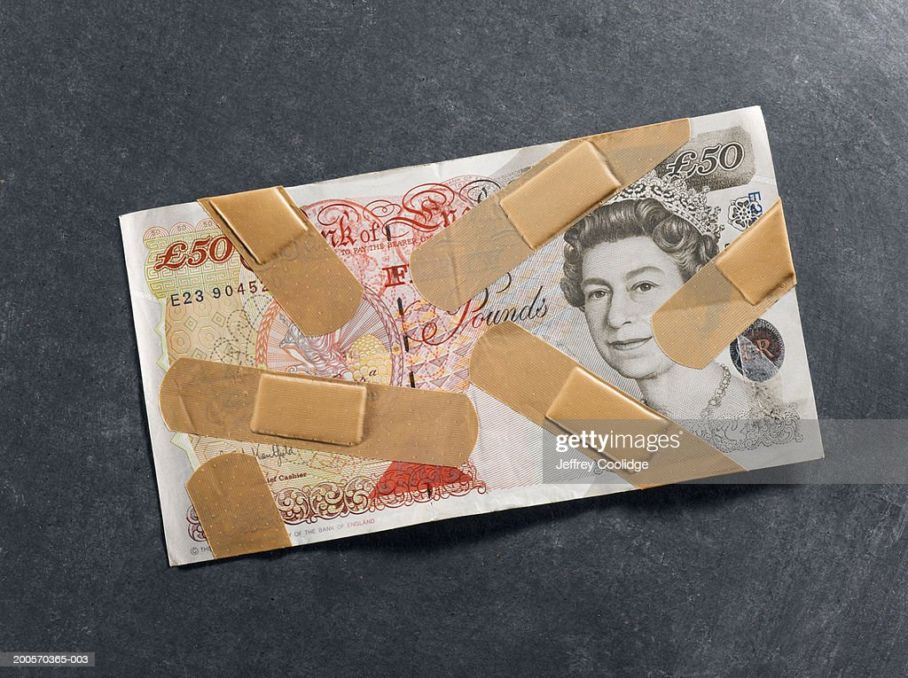 Bandages on fifty-pound note, overhead view : Stockfoto