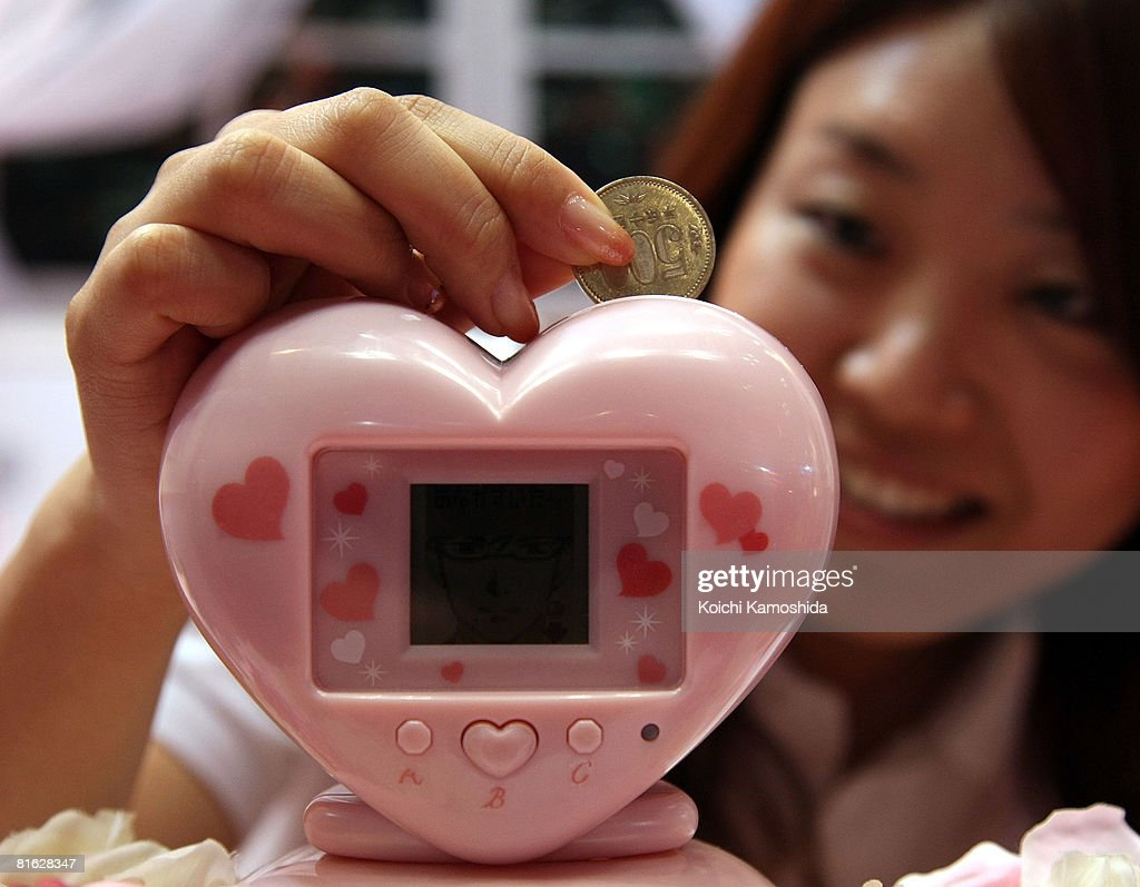 Bandai Co's employee displays the electronic piggybank 'ikemenbank' during the International Tokyo Toy Show at Tokyo Big Sight on June 19, 2008 in Tokyo, Japan. 'Ikemenbank', or 'handsome men bank' is an electronic piggy bank which the owners enjoy a virtual love affair with good-looking male cartoon character on LCD screen. 120,000 people are expected to visit the show over the 4 days which has 134 toy manufacturers from both Japan and abroad showing 36,000 products.