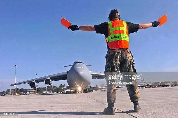 Bandanaike , Sri Lanka - Crew chief marshals a C-5 Galaxy aircraft that landed at the international airport supporting Operation Unified Assistance.
