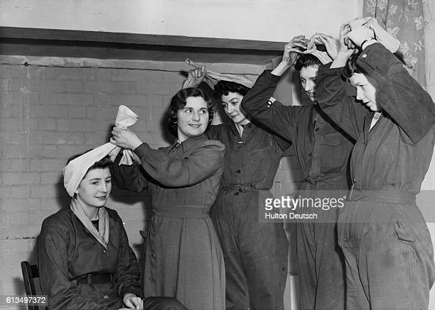 A Bandeaux Women workers of the Royal Ordnance Factory receive a lesson in tying their bandeaux Women workers in the huge Royal Ordnance Factories of...