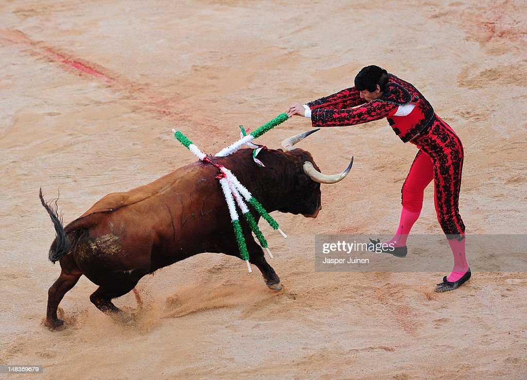 A banderillo jumps to plant banderillas in an El Pilar fighting bull during a bullfight of Spanish matador David Mora on the fourth day of the San Fermin running-of-the-bulls on July 10, 2012 in Pamplona, Spain.