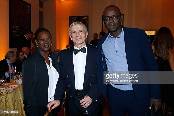 Bandmaster of the event Francois Boulanger standing between Football player Lilian Thuram and his sister Liliana Thuram attend the 24th 'Gala de...