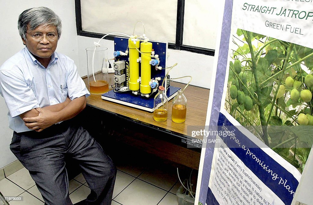 Indonesian professor Robert Manurung, head of the biotechnology research centre at the Bandung Institute of Technology (ITB), sits next to the sample of jatropha oil and the poster of its seed in Bandung, 13 September 2006. Indonesia's first fully plant-fuelled car has successfully completed a 3,200-kilometre (2,000-mile) road trip. Now its backers are hoping the triumph may herald a new era of sustainable energy in the archipelago nation. The car, fuelled with oil from the jatropha plant, smoothly negotiated the freezing volcanic peaks of Flores and Sumbawa islands, as well as the sweltering Javanese countryside. AFP PHOTO/Banyu SAKTI