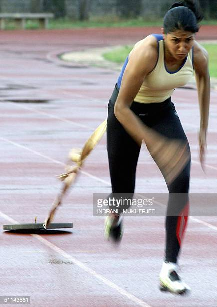 In this file photo taken 27 April 2004 Indian long jumper Anju Bobby George performs runs while dragging a weight behind her at the Sports Authority...
