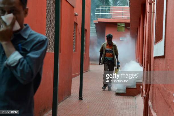 A Bangalore municipal worker fumigates an area in a bid to kill off mosquitos as a man covers his face in Bangalore on July 18 2017 Over 18700 cases...