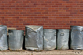 line of metal trash cans against a red brick wall