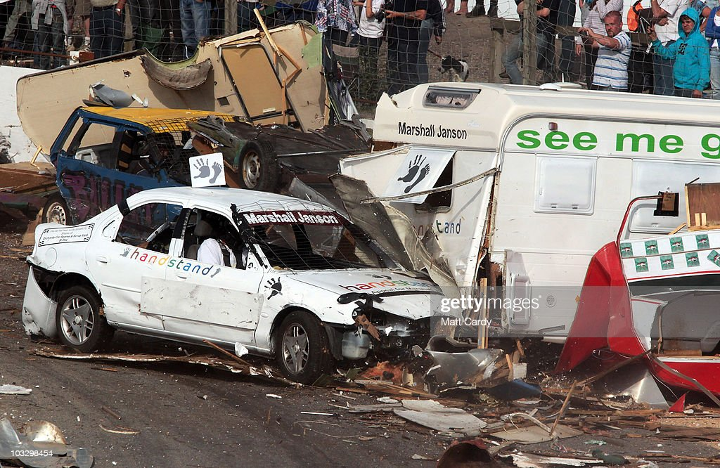 A banger racer crashes into a wreckage of old caravans destroyed in the annual Cornish Caravan Chaos at United Downs Raceway on August 8 2010 near...