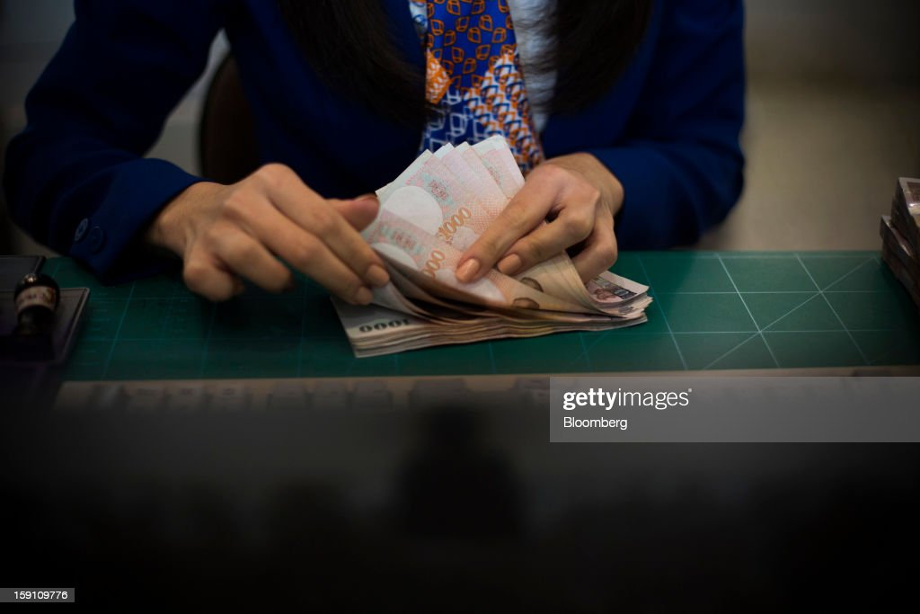 A Bangkok Bank Pcl. teller counts Thai 1000 Baht banknotes at the company's headquarters in Bangkok, Thailand, on Tuesday, Jan. 8, 2013. Thailand's economy may have expanded 5.7 percent in 2012 and will grow 5 percent in 2013, the finance ministry said on Dec. 26. Photographer: Brent Lewin/Bloomberg via Getty Images