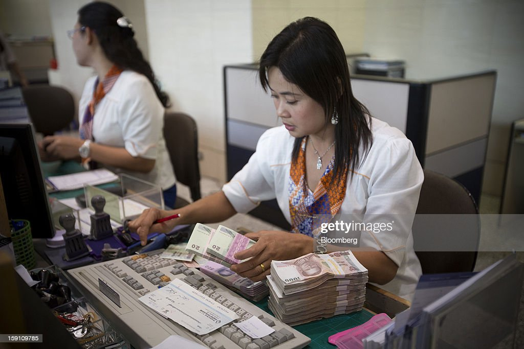 A Bangkok Bank Pcl. teller counts Thai Baht banknotes at the company's headquarters in Bangkok, Thailand, on Tuesday, Jan. 8, 2013. Thailand's economy may have expanded 5.7 percent in 2012 and will grow 5 percent in 2013, the finance ministry said on Dec. 26. Photographer: Brent Lewin/Bloomberg via Getty Images