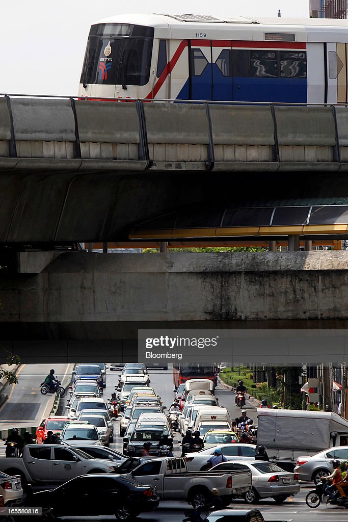 A Bangkok Mass Transit System Pcl SkyTrain, a unit of BTS Group Holdings Pcl, travels on an elevated track as traffic moves through the Chong Nonsi intersection in central Bangkok, Thailand, on Thursday, April 4, 2013. The BTS Rail Mass Transit Growth Infrastructure Fund, backed by Bangkok's SkyTrain, raised about 62.5 billion baht ($2.1 billion) in Thailand's biggest initial public offering. Photographer: Dario Pignatelli/Bloomberg via Getty Images
