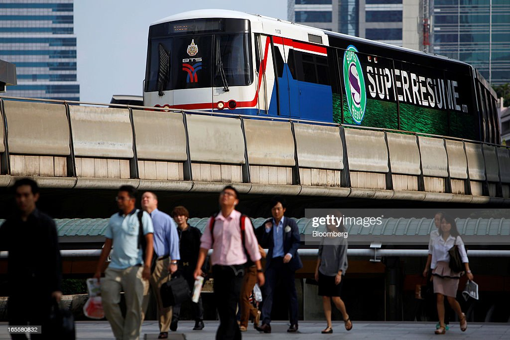 A Bangkok Mass Transit System Pcl SkyTrain, a unit of BTS Group Holdings Pcl, travels on an elevated track above the Chong Nonsi intersection as commuters walk on a pedestrian bridge in central Bangkok, Thailand, on Thursday, April 4, 2013. The BTS Rail Mass Transit Growth Infrastructure Fund, backed by Bangkok's SkyTrain, raised about 62.5 billion baht ($2.1 billion) in Thailand's biggest initial public offering. Photographer: Dario Pignatelli/Bloomberg via Getty Images