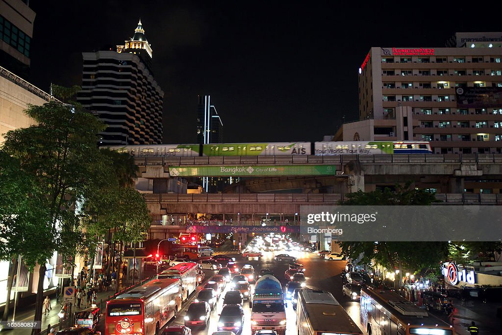 A Bangkok Mass Transit System Pcl SkyTrain, a unit of BTS Group Holdings Pcl, travels on an elevated track as traffic moves through the Rachadamnoen intersection at night in central Bangkok, Thailand, on Thursday, April 4, 2013. The BTS Rail Mass Transit Growth Infrastructure Fund, backed by Bangkok's SkyTrain, raised about 62.5 billion baht ($2.1 billion) in Thailand's biggest initial public offering. Photographer: Dario Pignatelli/Bloomberg via Getty Images
