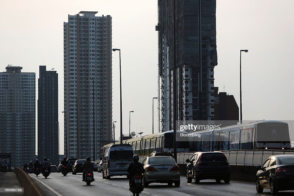 Bangkok Mass Transit System Pcl SkyTrains, a unit of BTS Group Holdings Pcl, travel alongside vehicles on the Saphan Thaksin bridge as residential buildings stand in Bangkok, Thailand, on Thursday, April 4, 2013. The BTS Rail Mass Transit Growth Infrastructure Fund, backed by Bangkok's SkyTrain, raised about 62.5 billion baht ($2.1 billion) in Thailand's biggest initial public offering. Photographer: Dario Pignatelli/Bloomberg via Getty Images