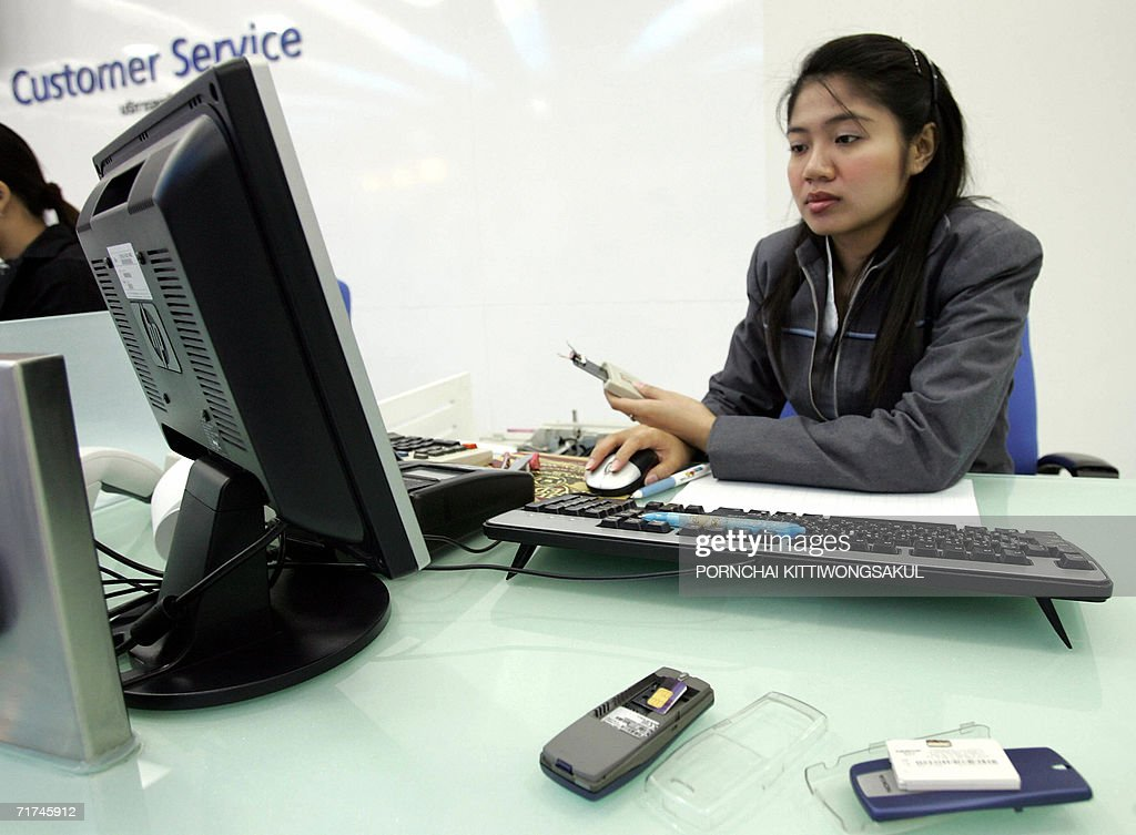 A mobile phone worker upgrades simcards for clients at a mobile phone shop in Bangkok, 30 August 2006. The Thai National Telecommunications Commission (NTC) is to introduce a new telephone numbering system on 01 September, which will see all mobile-phone numbers extended to 10 digits by adding the prefix 08.
